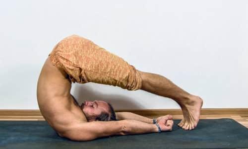 Для выполнения упражнения плуг необходимо лечь на спину, медленно поднять ноги в вертикальное положение, а затем опустить их за голову, отрывая таз от пола